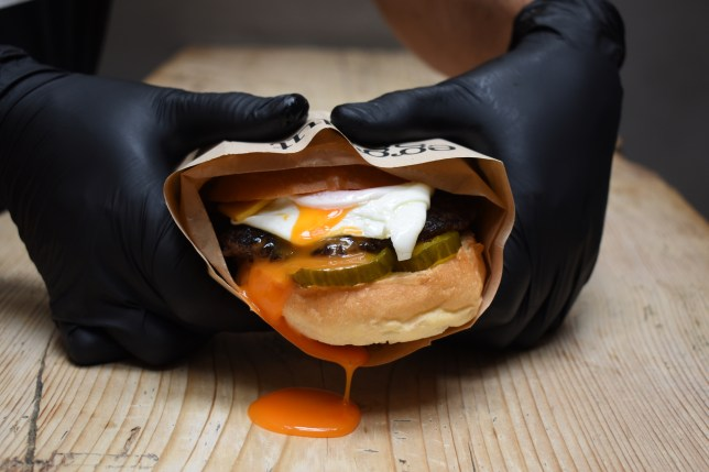 Egg with runny yolk in a sandwich held by two hands