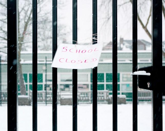 Sign on railings saying school closed.