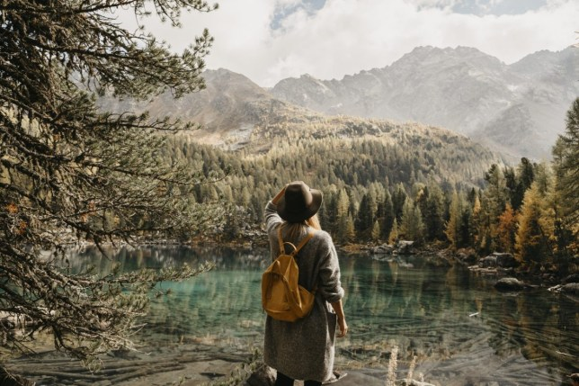 Switzerland, Engadin, woman on a hiking trip standing at lakeside in mountainscape