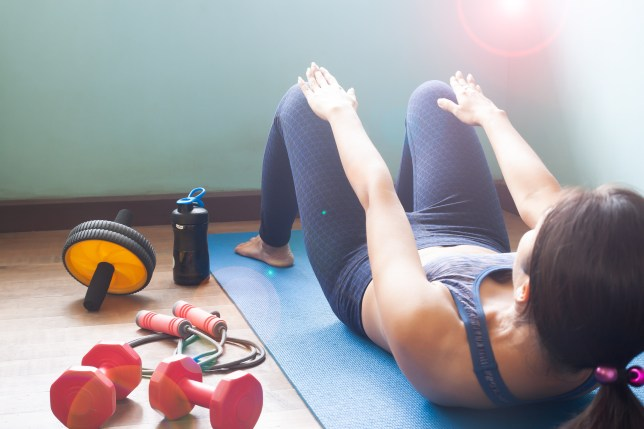 Woman Doing Sit-Ups On Exercise Mat At Home