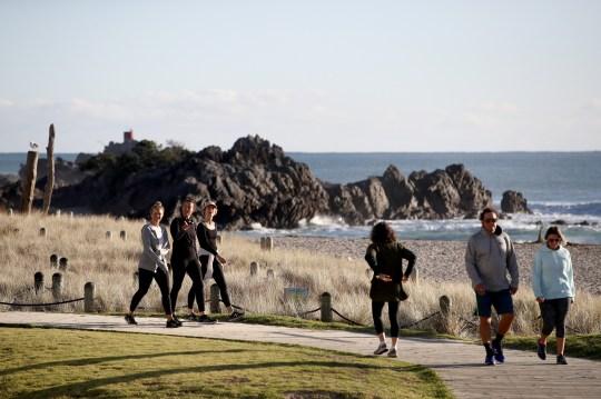 Les gens marchent le long de l'esplanade au-dessus de la plage au mont Maunganui.