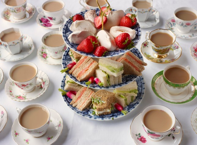 Vintage tea cups and sandwiches on a cake stand prepared for afternoon tea.