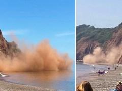 Cliffs crumble onto beach sending up huge cloud of dust