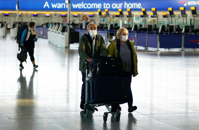 People wearing masks are seen at Heathrow airport, as the spread of the coronavirus disease (COVID-19) continues, London, Britain, April 5, 2020. REUTERS/Henry Nicholls