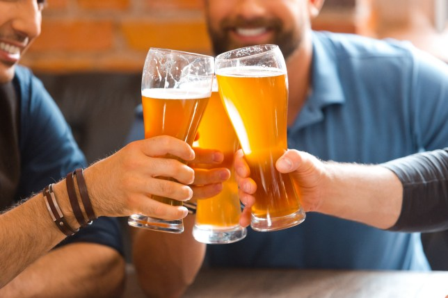 Three men drinking beer in the pub, toasting with beer glasses.