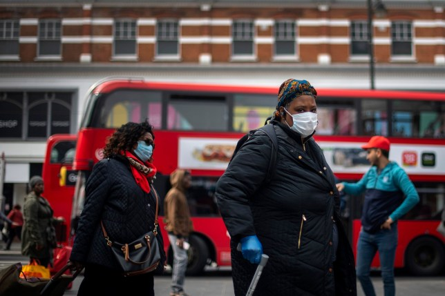 A woman in a protective face mask walks through Brixton Market in South London, as the UK continues in lockdown to help curb the spread of the coronavirus. PA Photo. Picture date: Thursday April 16, 2020. See PA story HEALTH Coronavirus. Photo credit should read: Victoria Jones/PA Wire