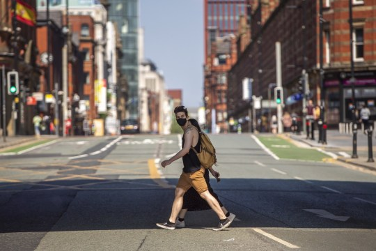 MANCHESTER, ENGLAND - APRIL 25: A man wears a face mask as he walks across Deansgate in central Manchester on April 25, 2020 in Manchester, United Kingdom. The UK government has extended the lockdown restrictions, which were first introduced on March 23, and are intended to support the spread of COVID-19. (Photo by Anthony Devlin / Getty Images)