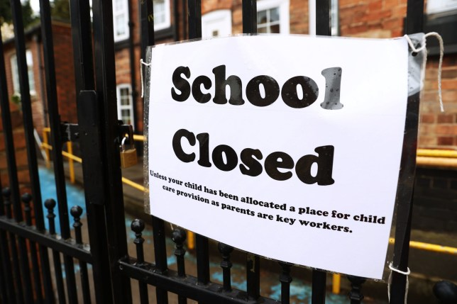 A school closed sign on a gate