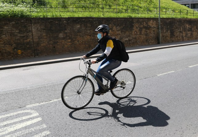 OXFORD, ENGLAND - MAY 02: A Cyclist rides while wearing a face mask on May 02, 2020 in Oxford, England. British Prime Minister Boris Johnson, who returned to Downing Street this week after recovering from Covid-19, said the country needed to continue its lockdown measures to avoid a second spike in infections. (Photo by Catherine Ivill/Getty Images)