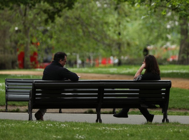 People observing social distancing on a bench in Hyde Park, London,