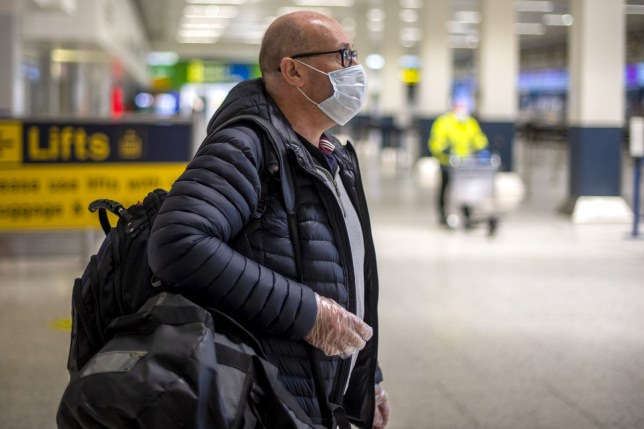 passengers at manchester airport wearing face masks