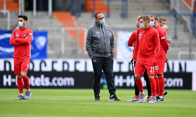 Players and manager wearing masks