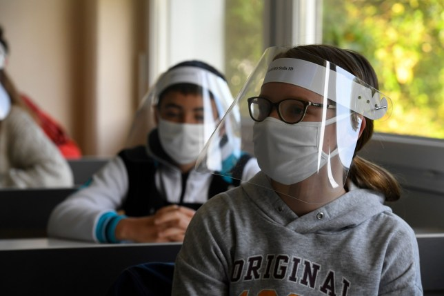 Schoolchildren wearing protective face masks and face shields
