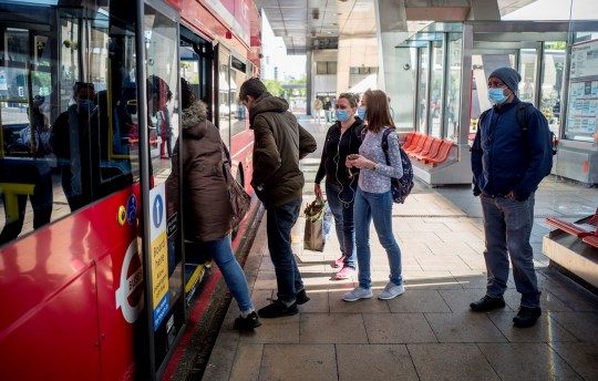 Commuters, some wearing PPE (personal protective equipment), including a face mask as a precaution against COVID-19, wait to board a red London TFL (Transport for London) bus at the station Vauxhall, central London, 18 May 2020. - Britain reported 170 more coronavirus deaths on Sunday - its lowest number since late March when lock-out restrictions were introduced, although the figures from Northern Ireland were not included. Prime Minister Boris Johnson has acknowledged public frustration with the restrictions imposed to fight the virus. (Photo by Tolga AKMEN / AFP) (Photo by TOLGA AKMEN / AFP via Getty Images)