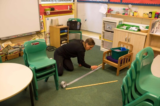 Teaching Assistant Sarah Yates applies tape to the floor to define a 2m boundary around the teacher's workspace as classrooms are altered to provide a teaching environment safe from Coronavirus for pupils and teachers at Marsden Infant and Nursery School in Marsden, near Huddersfield, northern England on May 18, 2020, ahead of the Government's proposed recommencing of education for Reception and Year 1 classes. - Marsden Infant and Nursery School is reducing class sizes to accommodate greater distancing between pupils as well as minimising any shared contact of stationery and learning materials. (Photo by OLI SCARFF / AFP) (Photo by OLI SCARFF/AFP via Getty Images)