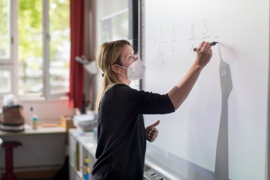 BERLIN, GERMANY - MAY 05: A teacher explains mathematics during a lesson with pupils (sixth graders), who are sitting at desks socially-distanced, on the second day of classes since March at an elementary school in the district Kreuzberg during the novel coronavirus crisis on May 5, 2020 in Berlin, Germany. Across Germany tenth graders began returning to school last week and elementary school pupils are returning this week in cautious steps to reopen schools that have been closed since March as authorities lift lockdown measures that had been imposed to stem the spread of the virus. (Photo by Christian Ender/Getty Images)