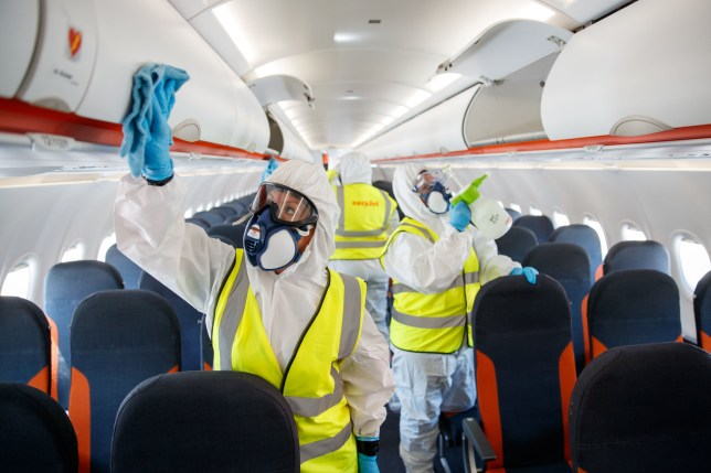 people cleaning the inside of a plane