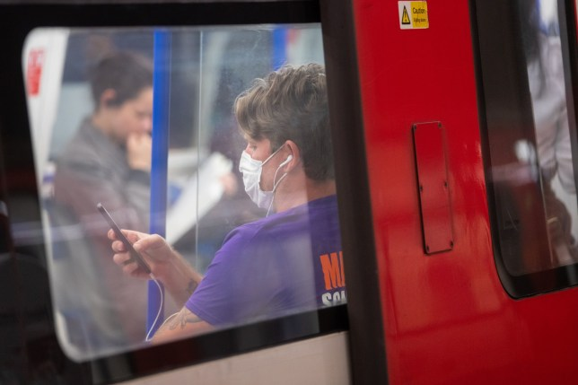 A commuter wearing a protective face mask at Clapham Common underground station, London, as train services increase this week as part of the easing of coronavirus lockdown restrictions. PA Photo. Picture date: Thursday May 21, 2020. See PA story HEALTH Coronavirus. Photo credit should read: Dominic Lipinski/PA Wire