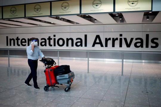 A passenger wearing a face mask and a visor as a precaution against the novel coronavirus arrive at Heathrow airport, west London, on May 22, 2020. - Travellers arriving in Britain will face 14 days in quarantine from next month to prevent a second coronavirus outbreak, the government announced on Friday, warning that anyone breaking the rules faced a fine or prosecution. (Photo by Tolga Akmen / AFP) (Photo by TOLGA AKMEN/AFP via Getty Images)