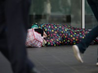 File photo dated 16/01/20 of people walking past a homeless man in London. Government homelessness investment is being fast-tracked to ensure more than 3,000 new homes for rough sleepers aided during the pandemic will be available in the next 12 months. PA Photo. Issue date: Sunday May 24, 2020. The move - which will see ?160 million of a ?381 million four-year pot brought forward to be spent this year - is a bid to prevent those taken off the streets during the pandemic returning to homelessness once it is over. See PA story HEALTH Coronavirus. Photo credit should read: Nick Ansell/PA Wire