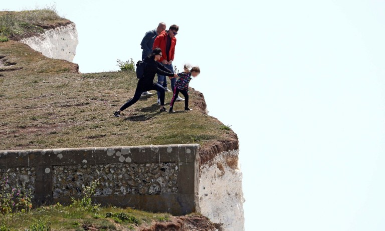 A young girl is pulled away from the edge of cliffs in Birling Gap, East Sussex