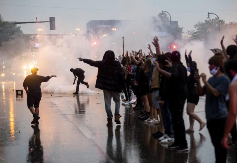Des gaz lacrymogènes sont tirés alors que des manifestants se heurtent à la police alors qu'ils manifestaient contre la mort de George Floyd à l'extérieur du 3e commissariat de police de Precinct le 26 mai 2020 à Minneapolis, Minnesota