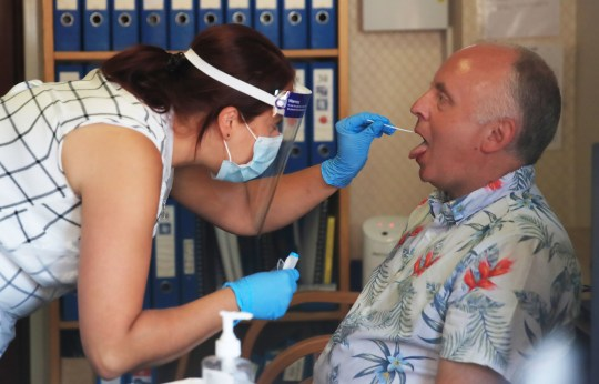 Assistant manager Claire Welford administers a coronavirus swab test on staff member Colin Scarr at the Eothen Homes care home in Whitley Bay, Tyneside, where all staff and residents are being tested for coronavirus. PA Photo. Issue date: Wednesday May 27, 2020. See PA story HEALTH Coronavirus. Photo credit should read: Owen Humphreys/PA Wire
