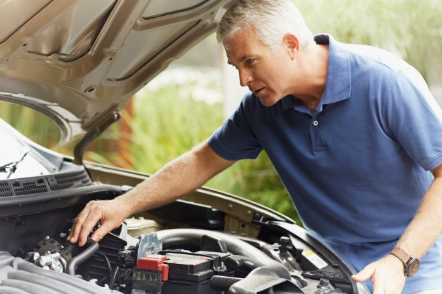 Concentrated mature man fixing his car engine outdoors