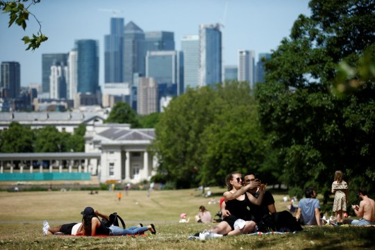 People enjoy the hot weather in Greenwich Park