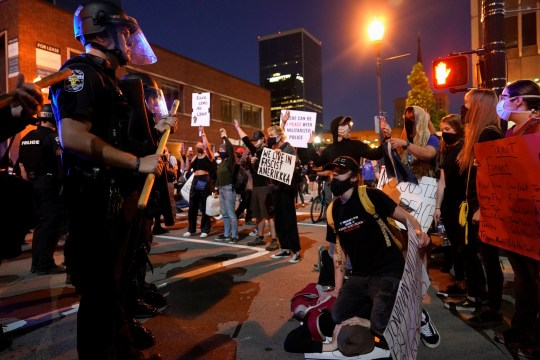 People reenact the pinning down of George Floyd by police, during a protest against the deaths of Breonna Taylor by Louisville police and George Floyd by Minneapolis police, in Louisville, Kentucky, U.S. May 29, 2020. REUTERS/Bryan Woolston