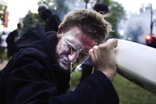 DENVER, CO - 30 MAI: Un homme qui avait des gaz lacrymogènes verse du lait dans ses yeux à côté du Colorado State Capitol alors que les manifestations contre la mort de George Floyd se poursuivent pour une troisième nuit le 30 mai 2020 à Denver, Colorado. La ville de Denver a imposé un couvre-feu pour les samedis et dimanches soirs et le gouverneur Jared Polis a activé la garde nationale du Colorado dans l'espoir d'arrêter les manifestations qui ont fait des ravages dans la ville.