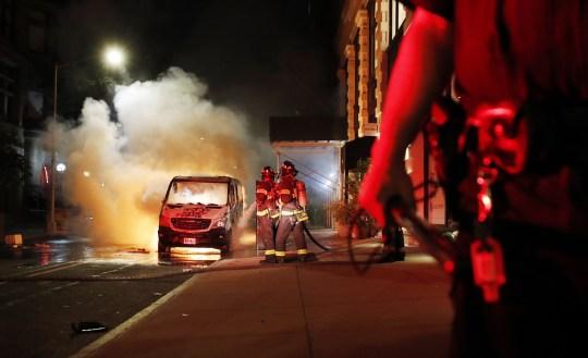 epaselect epa08455466 Un officier de police de la ville de New York monte la garde FDNY éteint une camionnette NYPD lors d'une manifestation sur l'arrestation de George Floyd, décédé plus tard en garde à vue, à New York, New York, USA, 30 mai 2020. Un passant la vidéo mise en ligne le 25 mai, semblait montrer à George Floyd, 46 ans, implorant les policiers qui l'arrêtaient de ne pas pouvoir respirer alors qu'un officier s'agenouillait au cou. L'homme noir non armé est décédé plus tard en garde à vue. EPA / JUSTIN LANE