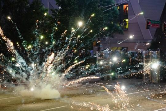 ATLANTA, GA - 30 MAI: Un feu d'artifice explose devant une ligne de police lors d'une manifestation en réponse au meurtre de George Floyd par la police le 30 mai 2020 à Atlanta, en Géorgie. Dans tout le pays, des manifestations ont éclaté à la suite du récent décès de George Floyd alors qu'il était en garde à vue à Minneapolis, au Minnesota, le plus récent d'une série de décès de Noirs américains par la police.