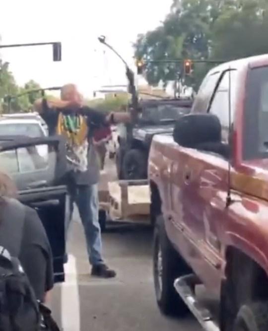 Un homme pointe un arc et une flèche sur une foule lors de troubles à l'échelle nationale après la mort de George Floyd en garde à vue à Minneapolis, à Salt Lake City, Utah, États-Unis, le 30 mai 2020, dans cette image fixe obtenue à partir d'une vidéo sur les réseaux sociaux.