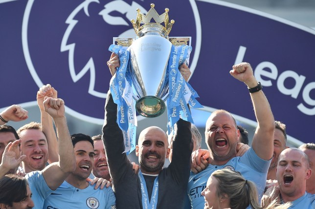 TOPSHOT - Manchester City's Spanish manager Pep Guardiola holds up the Premier League trophy as he's surrounded by his staff after their 4-1 victory in the English Premier League football match between Brighton and Hove Albion and Manchester City at the American Express Community Stadium in Brighton, southern England on May 12, 2019. - Manchester City held off a titanic challenge from Liverpool to become the first side in a decade to retain the Premier League on Sunday by coming from behind to beat Brighton 4-1 on Sunday. (Photo by Glyn KIRK / AFP) / RESTRICTED TO EDITORIAL USE. No use with unauthorized audio, video, data, fixture lists, club/league logos or 'live' services. Online in-match use limited to 120 images. An additional 40 images may be used in extra time. No video emulation. Social media in-match use limited to 120 images. An additional 40 images may be used in extra time. No use in betting publications, games or single club/league/player publications. / GLYN KIRK/AFP/Getty Images