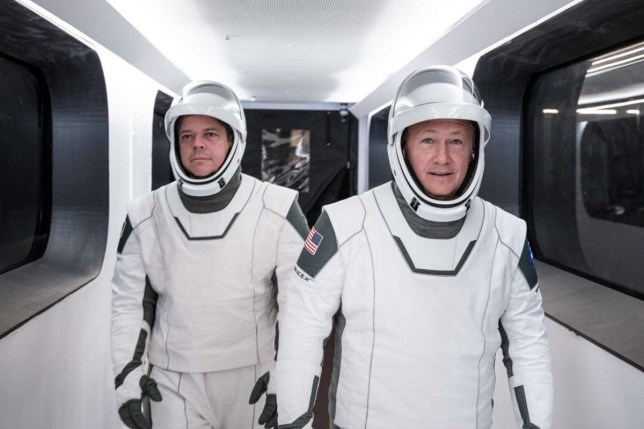Nasa astronauts Bob Behnken, left, and Doug Hurley, wearing SpaceX spacesuits, walk through the Crew Access Arm connecting the launch tower to the SpaceX Crew Dragon spacecraft during a dress rehearsal at Nasa's Kennedy Space Center in Florida (SpaceX)
