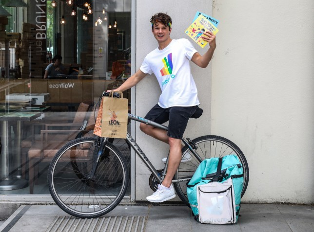 Author Olly Pike sat on a Deliveroo bike holding his LGBT book, written for children