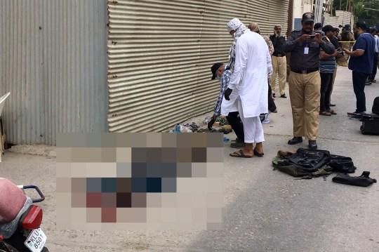 SENSITIVE MATERIAL. THIS IMAGE MAY OFFEND OR DISTURB A body lies on the ground as police officers, some in plainclothes, survey the site of an attack outside Pakistan Stocks Exchange in Karachi June 29, 2020. REUTERS/Akhtar Soomro