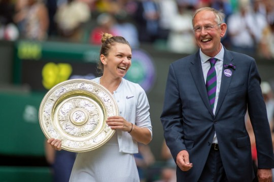 Simona Halep of Romania with the trophy escorted on a lap of honour by Richard Lewis, Chief Executive Officer at Wimbledon after her victory against Serena Williams of the United States during the Ladies Singles Final on Centre Court during the Wimbledon Lawn Tennis Championships at the All England Lawn Tennis and Croquet Club at Wimbledon on July 13, 2019 in London, England.
