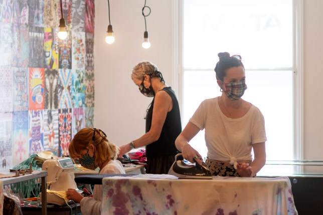 Volunteers work in a face masks design studio