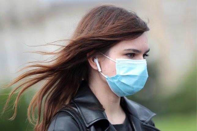 A woman walks in a street wearing a face mask.
