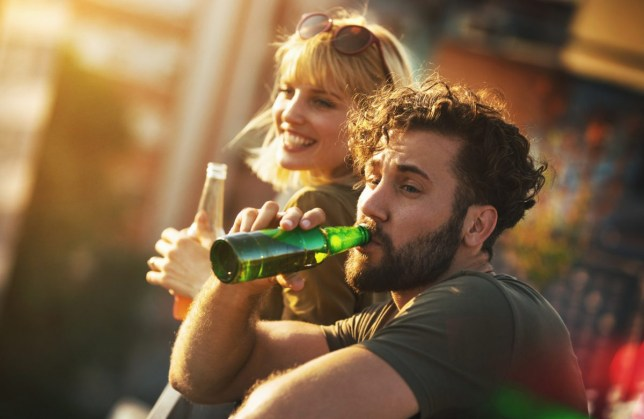 Rooftop party on a summer afternoon, man and woman drinking beer