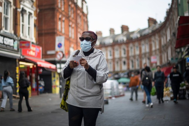 A woman in a protective face mask walks through Brixton Market in South London