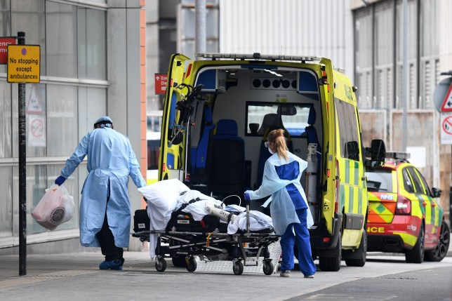 Health workers wear PPE as they transfer a patient into from an ambulance into The Royal London Hospital in east London on April 18, 2020, during the novel coronavirus COVID-19 pandemic. - Britain's death toll from the coronavirus rose by 847 on Friday, health ministry figures showed, a slightly slower increase than the previous day but still among the worst rates globally. (Photo by DANIEL LEAL-OLIVAS / AFP) (Photo by DANIEL LEAL-OLIVAS/AFP via Getty Images)