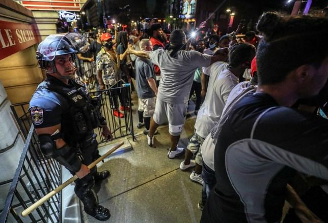 Des manifestants entourent un officier du LMPD devant Bearno lors d'une manifestation pour Breonna Taylor, le jeudi 28 mai 2020 à Louisville, Ky. Taylor, ?? une femme noire, a été tuée par balle par la police à son domicile en mars. Les organisateurs de la manifestation ont entouré l'officier et ont joint les bras pour s'assurer que le chanteur ne le touchait pas. (Michael Clevenger / Courier Journal via AP) 8368411 La mère de la police de Louisville tire sur la victime qui appelle à la paix
