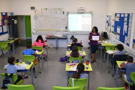 A teacher instructs Year 6 pupils in a classroom with other pupils participating by video conference at the College Francais Bilingue De Londres French-English bilingual school in north London on June 2, 2020 as schools in England partially reopen from coronavirus shutdown. - Schools partially reopened in England on June 2 and the most vulnerable were allowed to venture outdoors, despite warnings that the world's second worst-hit country was moving too quickly out of its coronavirus lockdown. (Photo by DANIEL LEAL-OLIVAS / AFP) (Photo by DANIEL LEAL-OLIVAS/AFP via Getty Images)