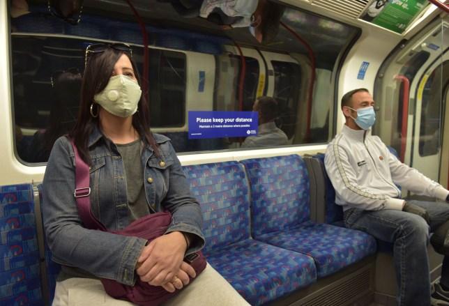 Les passagers portent des masques sur un train souterrain de la Central Line