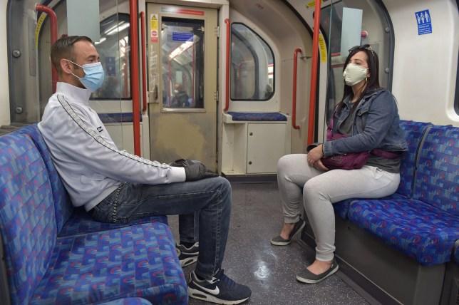 Passengers wear face masks on an underground train