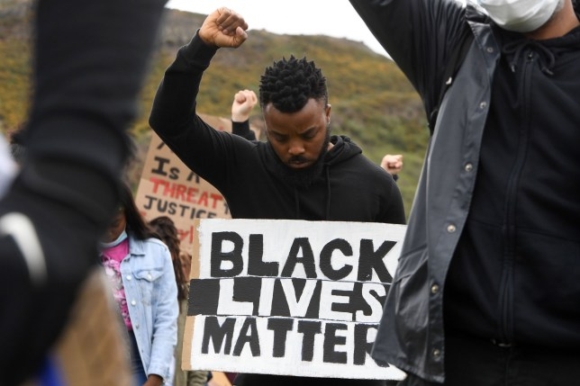 Protesters makes Black Lives Matter fists at a demonstration in Edinburgh