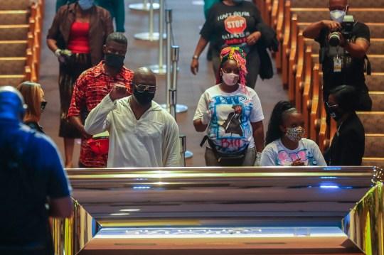 Les personnes en deuil sont guidées dans la fontaine de la louange lors d'une visite publique pour George Floyd le lundi 8 juin 2020 à Houston. Floyd est décédé après avoir été retenu par des policiers de Minneapolis le 25 mai. (Godofredo A. V ?? squez, Houston Chronicle via AP, Pool)